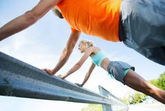 Stock Photo of close up of happy couple doing push-ups outdoors