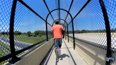 Young healthy African American guy jogging on bridge outdoors - stock footage