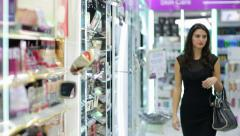 Young woman choosing cosmetics in the beauty shop Stock Footage