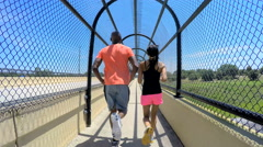 Young active African American male and female jogging on walkway outdoors - stock footage