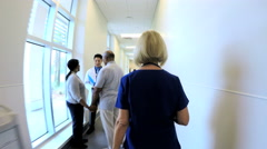 Blonde senior Caucasian American female nurse walking corridor in medical center Stock Footage