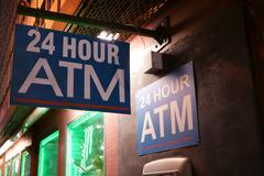 24 Hour ATM sign on side of store on a dark alley Stock Photos