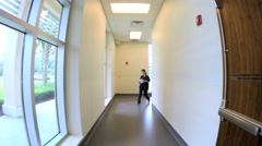 Young Chinese American female doctor walking corridor in hospital - stock footage