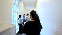 Young Asian American female staff walking corridor in medical centre Stock Footage
