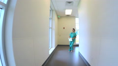 Young Caucasian American female staff walking corridor in medical center Stock Footage