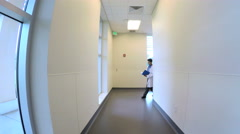 Young Asian American male doctor walking corridor in medical center - stock footage