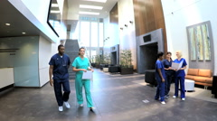 Stock Video Footage of Multi ethnic professional staff wearing scrubs in medical center atrium
