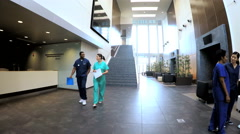Multi ethnic professional staff wearing scrubs in medical center reception - stock footage