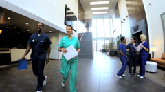 Multi ethnic professional staff consulting in medical centre entrance Stock Footage