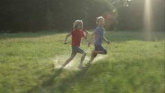 Two happy kids run over field in sunshine Stock Footage