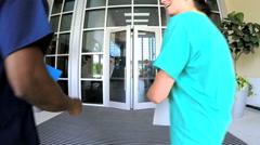 Multi ethnic professional nurses consulting in medical centre atrium - stock footage