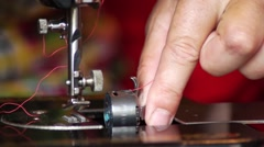 The woman inserts the bobbin and pull the thread - stock footage
