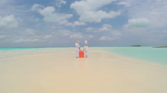 Caucasian retired travel seniors in white clothes with suitcase on beach - stock footage