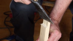 Man cleaves pieces of wood from the board using ax indoors Stock Footage