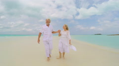 Barefoot retired senior couple happy together on tropical beach - stock footage