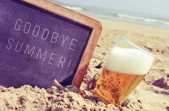 text goodbye summer in a chalkboard and a glass of beer on the beach - stock photo
