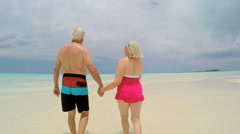 Loving Caucasian senior couple in swimwear on tropical vacation beach - stock footage