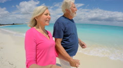 Retired Caucasian seniors in casual clothing taking a selfie on beach - stock footage