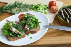 sprats, bread, onion and tomatoes on a table - stock photo