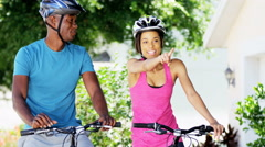 Young active African American girl and guy enjoying biking outdoor - stock footage