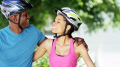 Portrait of young happy African American couple enjoying bike ride outdoors - stock footage