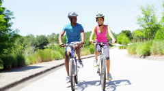 Young active African American couple cycling to keep fit outdoors - stock footage