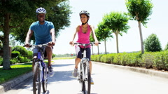 Young fit African American guy and girl cycling to keep healthy outdoors - stock footage