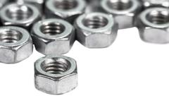 Closeup metal screw (bolt) and nuts on white background. - stock photo