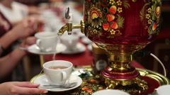 Woman pours boiling water from the samovar into a cup Stock Footage