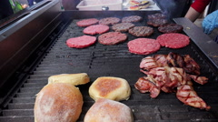 Burger shop - hamburgers with bacon and bread on grill Stock Footage