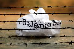 Balance crinkled paper against barbwire - stock photo