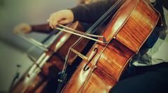 Symphony orchestra on stage, hands playing cello - stock photo
