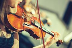 Symphony orchestra on stage, hands playing violin - stock photo