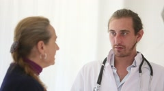 Young doctor speaks to a patient Stock Footage
