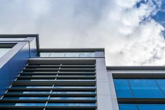 Upright Modern Office Building with White Clouds Stock Photos