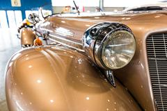rounded lines and round headlights of a vintage car - stock photo