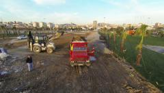 Excavator loading soil on a dump truck. View from aerial camera Stock Footage