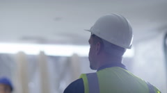 4k Architect or construction worker at building site looks around the building - stock footage