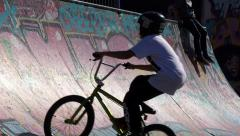 Skaters and bmx bikers in a skateboard park Stock Footage