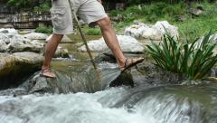 Hiker hopping across rocks in river rapids - stock footage