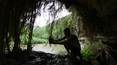 Hiker collecting water dripping from cave Stock Footage