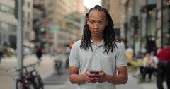 Young African American Black Asian mixed man walking and texting on city street Stock Footage