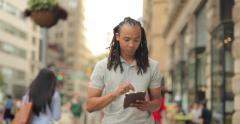 Young African American Black Asian mixed man walking using tablet Stock Footage