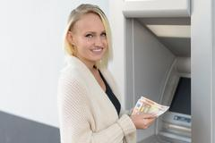 Stylish woman drawing money at a bank ATM Stock Photos