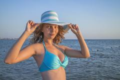 Portrait of a girl in a hat at sea - stock photo