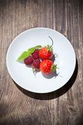 rapsberry and strawberry on whitte plate and wood table - stock photo