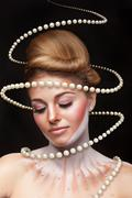 Surreal art concept of girl with pearls arround her - stock photo
