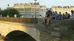 People sitting on the Pont de l'Archeveche bridge - Paris France Stock Footage