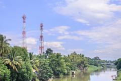 Mobile telephone antenna near river. - stock photo