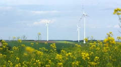 Alternative energy sources: windmills and canola flowers field Stock Footage